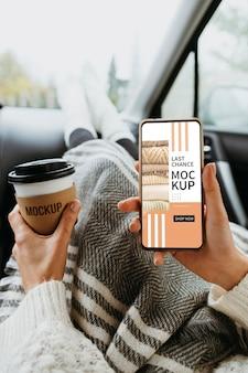 Bovenaanzicht bij de hand met smartphonemodel en kopje koffie