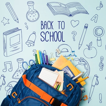Bovenaanzicht blauwe schooltas met benodigdheden