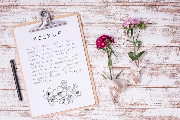 Bovenaanzicht bloemen met klembord mock-up Gratis Psd