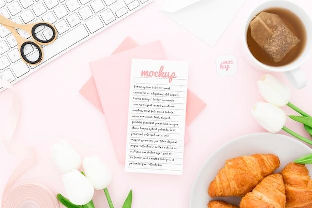 Bovenaanzicht bureau met croissants en telefoonmodel