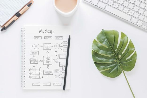 Bovenaanzicht bureau met kladblok en koffie