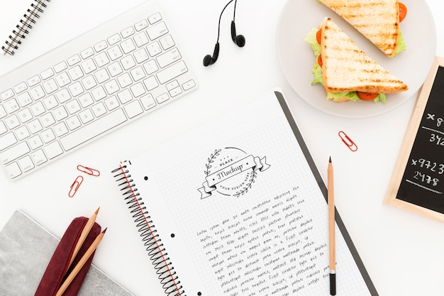Bovenaanzicht bureau met sandwich en notebook mock-up