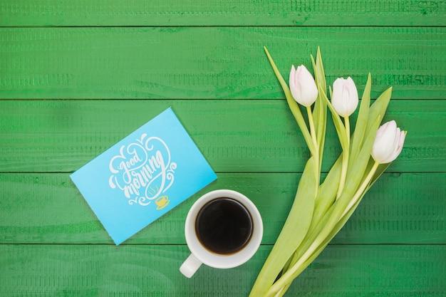 Bovenaanzicht collectie koffiekopje naast bloemen