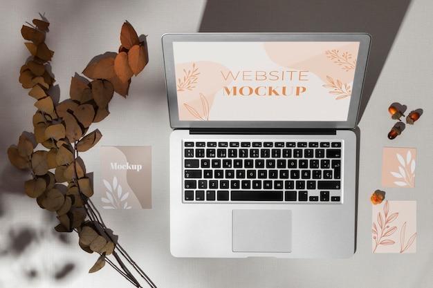 Bovenaanzicht geopende laptop met schermmodel naast bladeren