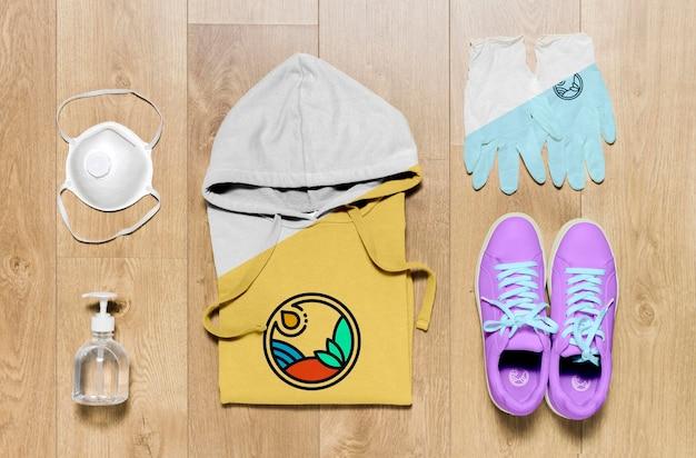 Bovenaanzicht gevouwen hoodie mock-up met handdesinfecterend middel, masker en handschoenen