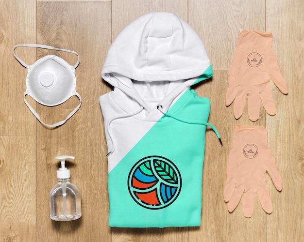 Bovenaanzicht gevouwen hoodie mock-up met handschoenen en handdesinfecterend middel