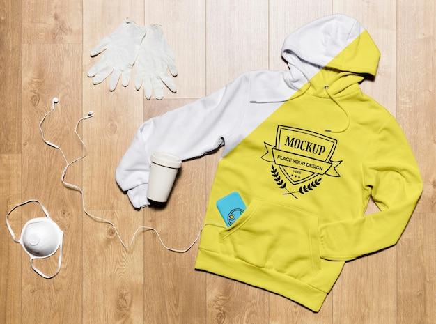 Bovenaanzicht hoodie mock-up met koffiekopje, beschermende handschoenen en masker