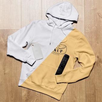 Bovenaanzicht hoodie mock-up met telefoonhoes en tv-afstandsbediening