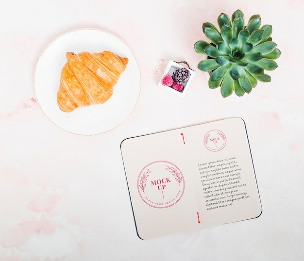 Bovenaanzicht kamerplant met croissant op tafel