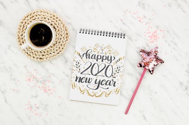 Bovenaanzicht kopje koffie en kladblok met nieuwjaar citaat
