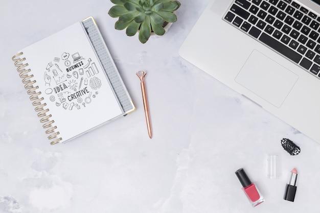 Bovenaanzicht laptop op een tafel met kladblok