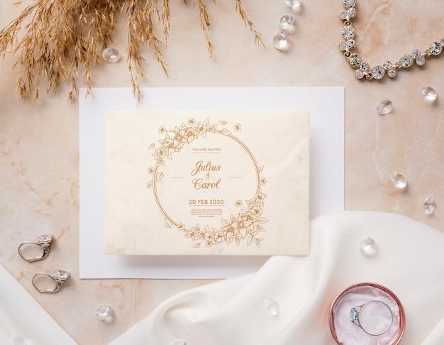 Bovenaanzicht mooie opstelling van bruiloft elementen met uitnodiging mock-up