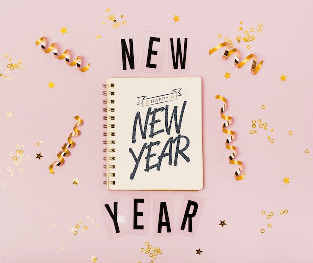 Bovenaanzicht nieuwjaar minimalistische letters op kladblok