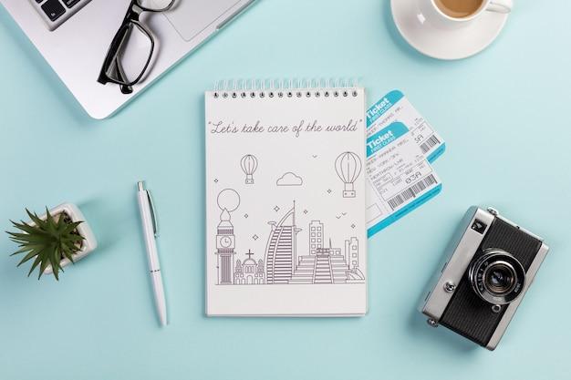 Bovenaanzicht notebook met vliegtickets en camera