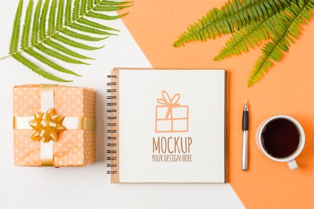 Bovenaanzicht notebook mock-up naast verjaardagscadeau