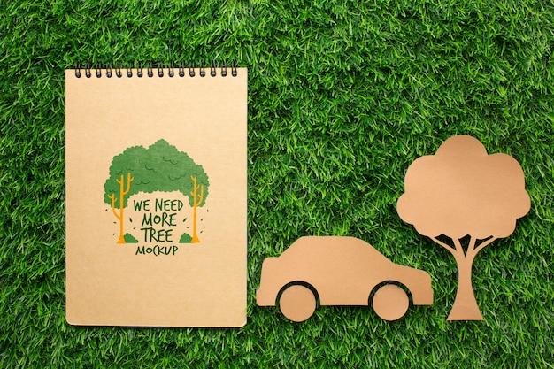 Bovenaanzicht notebookmodel en papieren auto en boom
