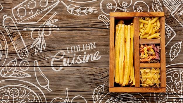 Bovenaanzicht ongekookte pasta in houten doos op hand getrokken achtergrond