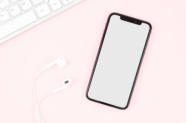 Bovenaanzicht oortelefoons en smartphone mock-up