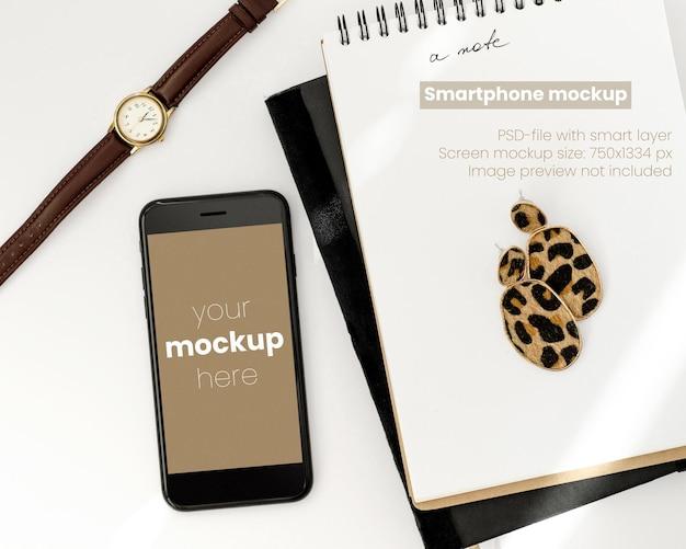 Bovenaanzicht op wit bureaublad met smartphonemodel