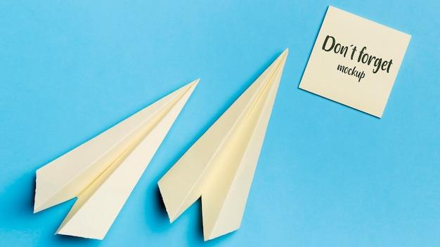 Bovenaanzicht papieren vliegtuig en notitie met mock-up