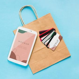 Bovenaanzicht papieren zakmodel met mobiele telefoon en kaarten