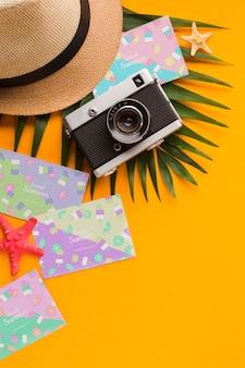 Bovenaanzicht reizen hoed met zomer kaarten en camera