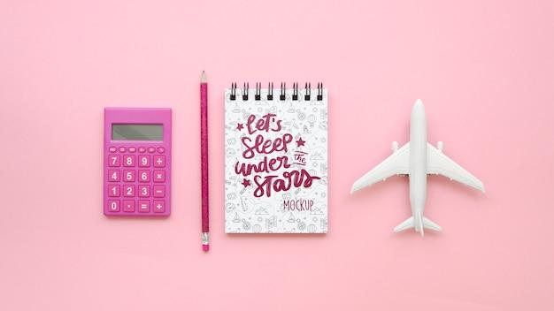 Bovenaanzicht reizend vliegtuig en roze calculator