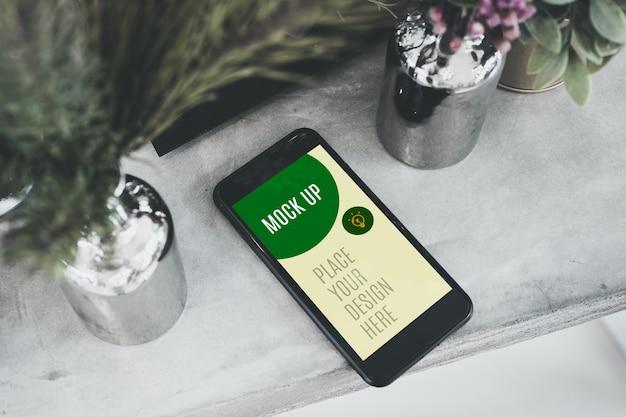 Bovenaanzicht scherm mobiele mockup op betonnen tafel met plant in vaas.
