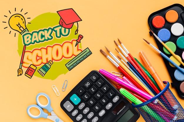 Bovenaanzicht schoolbenodigdheden met oranje achtergrond