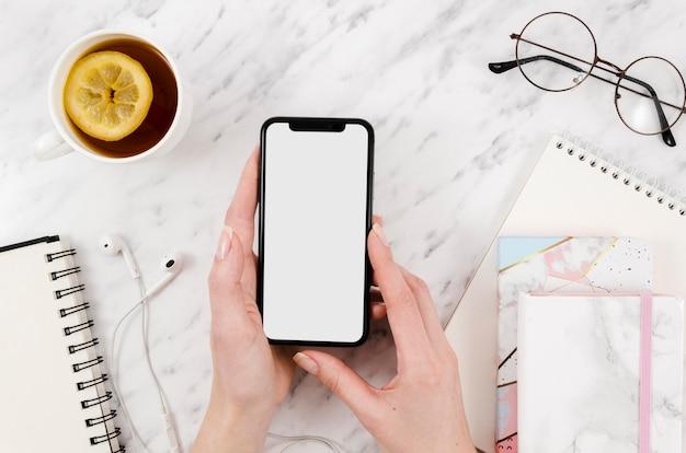 Bovenaanzicht smartphone mock-up met thee en glazen