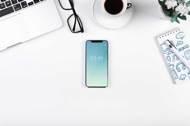 Bovenaanzicht smartphone mockup op de werkruimte