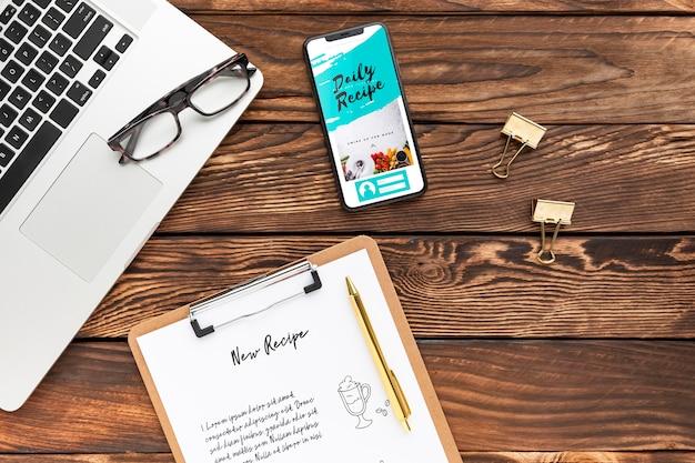 Bovenaanzicht telefoon- en notitieblokmodel met laptop