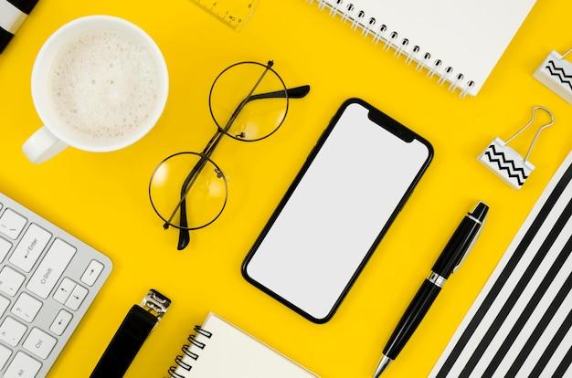 Bovenaanzicht telefoonmodel met bril en beker