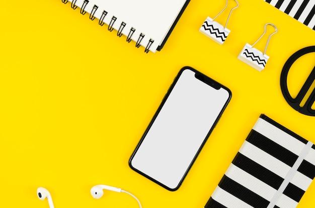 Bovenaanzicht telefoonmodel met kladblok en oortelefoons