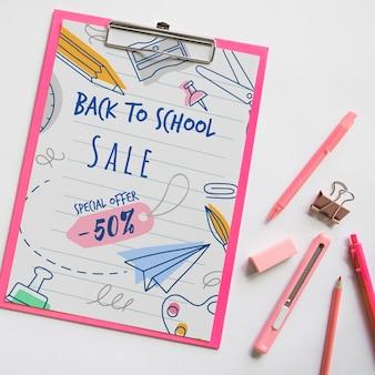 Bovenaanzicht terug naar schoolverkoop met klembord en benodigdheden