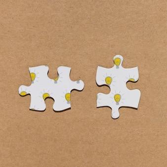 Bovenaanzicht twee puzzelstukjes op bruine achtergrond