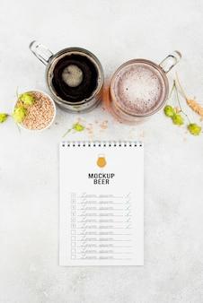 Bovenaanzicht van bierpinten met gerst en notitieboekje