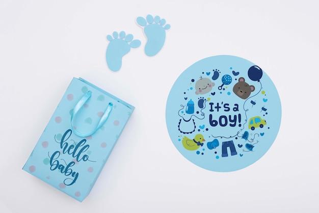Bovenaanzicht van blauwe baby douche decor met geschenk tas