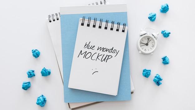 Bovenaanzicht van blauwe maandag notebooks met wekker
