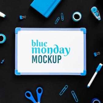 Bovenaanzicht van blauwe maandag whiteboard met briefpapier