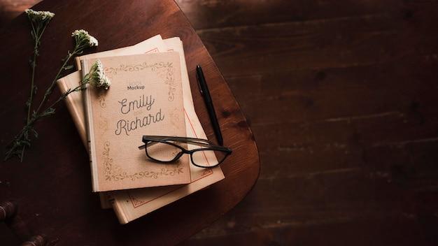 Bovenaanzicht van boeken met een bril en pen