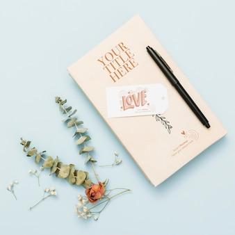 Bovenaanzicht van boekmodel met pen en bloemen