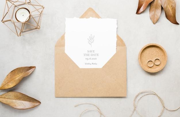 Bovenaanzicht van bruiloft kaart met envelop en bladeren
