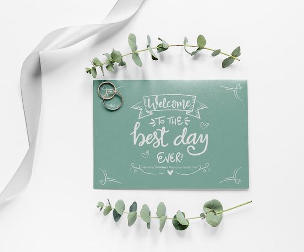 Bovenaanzicht van bruiloft kaart met planten en ringen