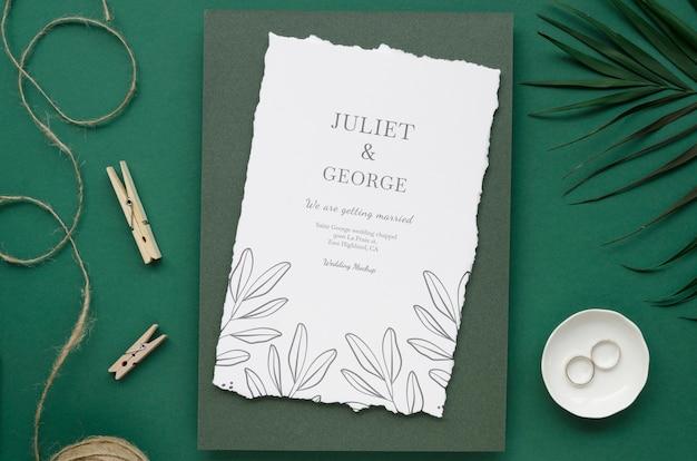 Bovenaanzicht van bruiloft kaart met ringen en kleding pinnen