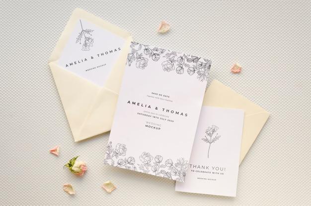 Bovenaanzicht van bruiloft kaart met roos en enveloppen