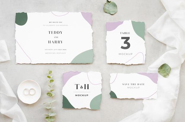 Bovenaanzicht van bruiloft kaarten met bladeren en ringen