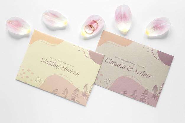 Bovenaanzicht van bruiloft kaarten met bloemblaadjes en ringen
