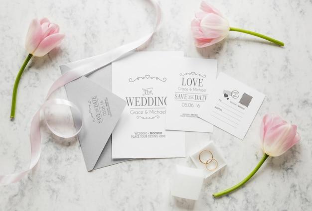 Bovenaanzicht van bruiloft kaarten met envelop en bloemen