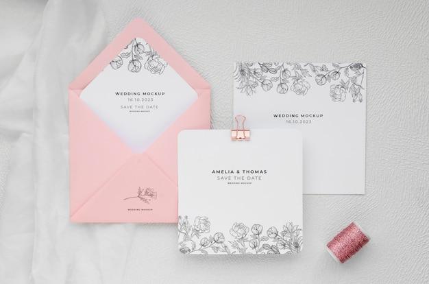 Bovenaanzicht van bruiloft kaarten met envelop en draad